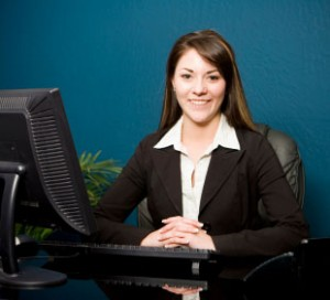 Receptionist in black dress sits at the computer in her leather chair, She is smiling at us.
