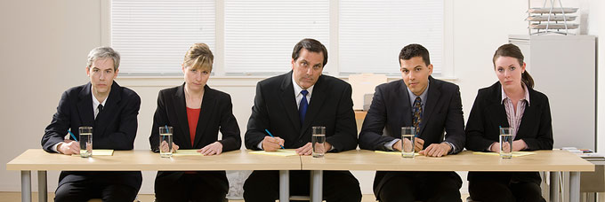 Panel of interviewers in a hotel, they look in a bad mood, interviewing a receptionist job applicant