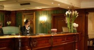 Receptionist is on a call, standing at a desk in a beautiful butique hotel. We can see some flowers and wooden furniture.