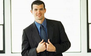 Nicely dressed job applicant, looking confident, wearing a blue shirt and a blue tie, and black jacket