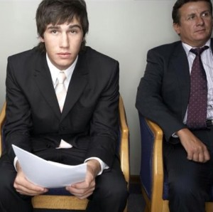 Nervous man before an interview in a hotel. He holds his resume in hand. We can see another man sitting next to him.